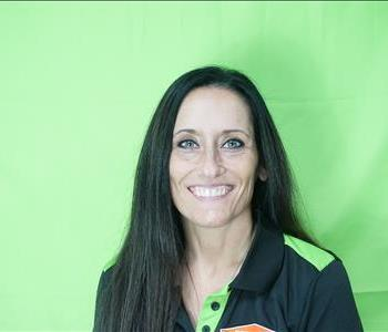 Female employee with black hair in front of green background