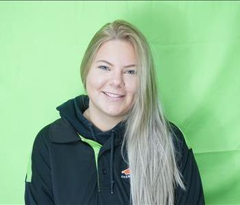 Female employee with blonde hair in front of green background