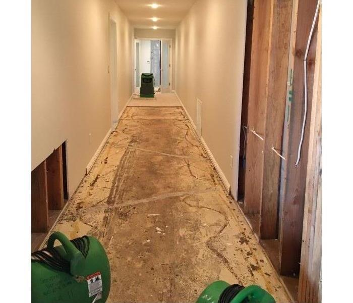 Servpro fans and dehumidifier dry hallway